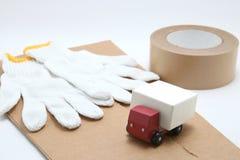 Mini camion dell'automobile del giocattolo, nastro d'imballaggio, cartongessi e guanti del lavoro del cotone su fondo bianco Fotografia Stock