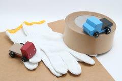 Mini camion dell'automobile del giocattolo, nastro d'imballaggio, cartongessi e guanti del lavoro del cotone su fondo bianco Fotografie Stock