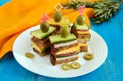 Mini canape con i cetrioli freschi, prosciutto, formaggio, olive, salame, pane nero dei panini fotografie stock