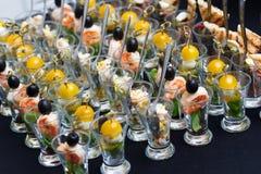 Mini Canape mit Fleisch und Gemüse in den zahlreichen Glasschalen Stockbilder