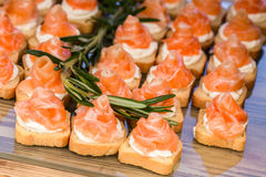 Mini canapes with smoked salmon and rosemary sprig. Stock Photos