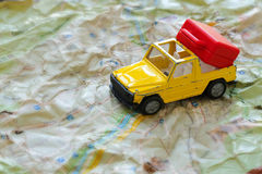 Mini car and a red plastic suitcase on a map. Closeup Royalty Free Stock Photos