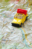 Mini car and a red plastic suitcase on a map. Closeup Stock Photos