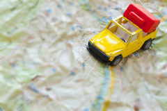 Mini car and a red plastic suitcase on a map. Closeup Stock Photo