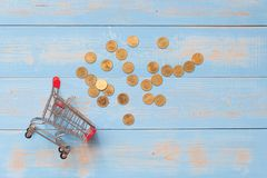 Mini carrinho de compras com as moedas na tabela de madeira azul negócio, finança, compra em linha e economia do dinheiro para o  foto de stock