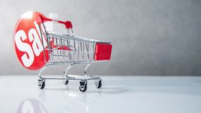 Mini carrinho de compras com etiqueta vermelha da venda imagens de stock