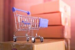 Mini carro de la compra azul con las cajas de cartón en fondo foto de archivo libre de regalías