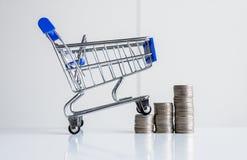 Mini carro de la compra con el paso de las pilas de las monedas, de las finanzas y del concepto de las compras del dinero imágenes de archivo libres de regalías