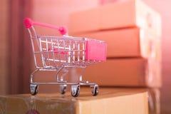 Mini carro de la compra rojo con las cajas de cartón en fondo foto de archivo libre de regalías