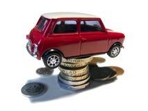 Mini carro vermelho do brinquedo na pilha das moedas foto de stock