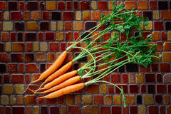 Mini Carrot vegetables on a tiles table Stock Photos