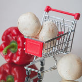 Mini cart shopping witch organic fresh vegetables and mushrooms on light background. Concept of healthy food shopping Royalty Free Stock Photos