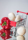 Mini cart shopping witch organic fresh vegetables and mushrooms on light background. Detox, diet, health or vegetarian Royalty Free Stock Image