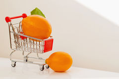 Mini cart, trolley shopping witch organic bright lemons on light background. Concept of healthy food shopping, detox royalty free stock images