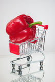 Mini cart, trolley shopping witch organic fresh vegetables, one ripe pepeer on light background. . Concept of healthy Stock Photo