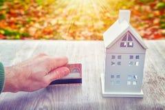Mini carte de crédit à la maison de modèle et de plastique dans la main du ` s de l'homme Paiements pour la maison Achetez le con Photo stock