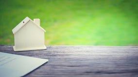 mini casa de madera y cuaderno en la tabla de madera con el fondo verde del copyspace del jardín Foto de archivo libre de regalías