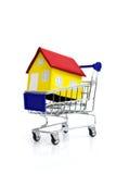 Mini casa en carro de la compra. Fotos de archivo