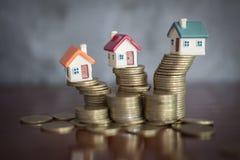 Mini casa en la pila de monedas, concepto de propiedad de la inversión, de riesgo de inversión y de incertidumbre en el mercado i imagen de archivo libre de regalías