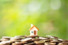 Mini casa sul mucchio delle monete immagine stock libera da diritti