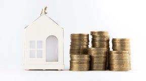 Mini casa sulla pila di monete Concetto della proprietà di investimento Alloggio sul credito Fotografia Stock