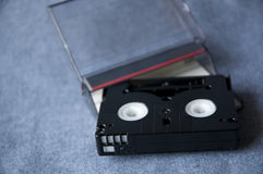 Mini cassette. Mini DV cassette tape and clear tape box on blue background Royalty Free Stock Image