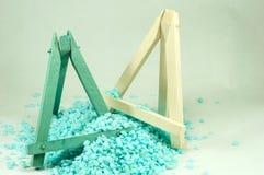 Mini cavalletti di legno blu e bianchi, che sono bombardati dalle piccole pietre blu Fotografie Stock Libere da Diritti