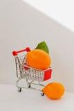 Mini chariot, citrons lumineux organiques de sorcière d'achats de chariot sur le fond clair Concept des achats de nourriture sain Images stock