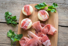 Mini cheese and prosciutto wraps on the wooden board Royalty Free Stock Image