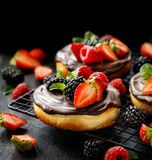 Mini cheesecake covered with chocolate with the addition of fresh berry fruits: blackberry, raspberry, strawberry, cherry and mint. On a cooling tray on a black royalty free stock images