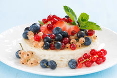 Mini cheesecake with fresh berries on a blue background Stock Images