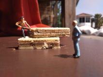 mini chiffre pile de creusement de travailleur raide de jouet des biscuits, commandée par son patron images libres de droits