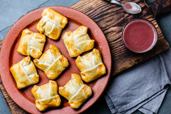 Mini chilean empanadas on clay plate with typical chilean drink vino con harina - red wine with toasted flour.  Stock Photos