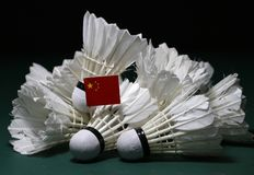 Mini China flag stick on the heap of used shuttlecocks on green floor of Badminton court. With dark black background stock photo