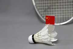 Mini China flag stick on the white shuttlecock on the grey background and out focus badminton racket. Concept of badminton sport stock photo