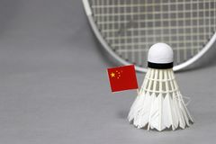 Mini China flag stick on the white shuttlecock on the grey background and out focus badminton racket. Concept of badminton sport stock image