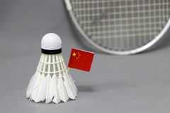 Mini China flag stick on the white shuttlecock on the grey background and out focus badminton racket. Concept of badminton sport royalty free stock images