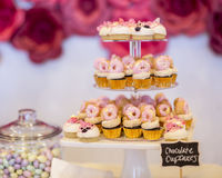Mini chocolate cupcakes topped with mini pink donuts on a desser Stock Photos