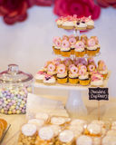 Mini chocolate cupcakes topped with mini pink donuts on a desser. T table. They are displayed on a tiered display tray. There is a cute chalkboard sign Stock Photos