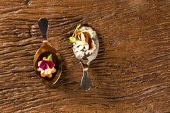 Mini churros salados y cerdo caramelizado acompañados por el arroz del jazmín y el curry rojo en una cuchara Fotografía de archivo
