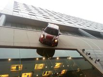 Mini Cooper driving down side of building royalty free stock photo