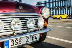Mini Cooper met gele Chevrolet-Korvetpijlstaartrog op achtergrond Stock Afbeeldingen