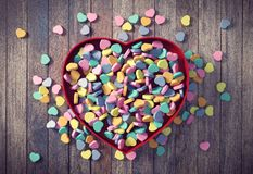 Mini corações dos Valentim coloridos na caixa vermelha do coração no fundo de madeira Foto de Stock