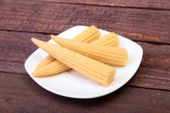Mini Corn majskolv som bevaras på plattan på träbräde Fotografering för Bildbyråer