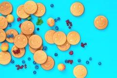 Mini crêpes délicieuses de sourire avec des baies sur la surface bleue Photos stock