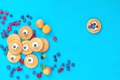 Mini crêpes délicieuses de sourire avec des baies sur la surface bleue Photographie stock libre de droits