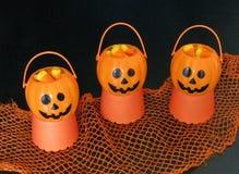 Mini cric-o-lanternes de sourire de Halloween tenant les bonbons au maïs colorés, sur un contexte noir et orange Photos libres de droits