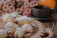 Mini croissant su una tavola di legno, bagel con una tazza di caffè su una tavola di legno, bagel su una tavola di legno fotografie stock libere da diritti