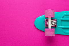 Mini cruiser board on deep pink back Royalty Free Stock Images