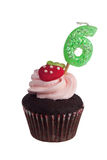 Mini cupcake with birthday candle for six year old. Isolated on white background Royalty Free Stock Images